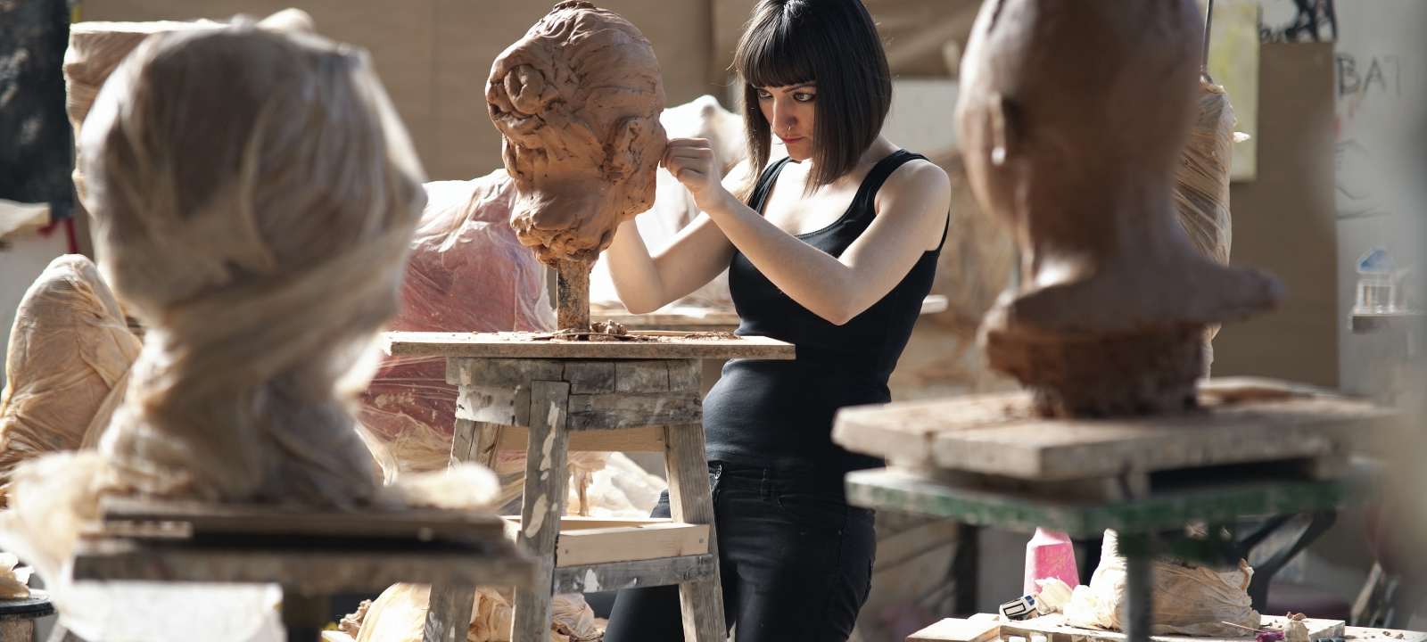 A lady sculpting heads